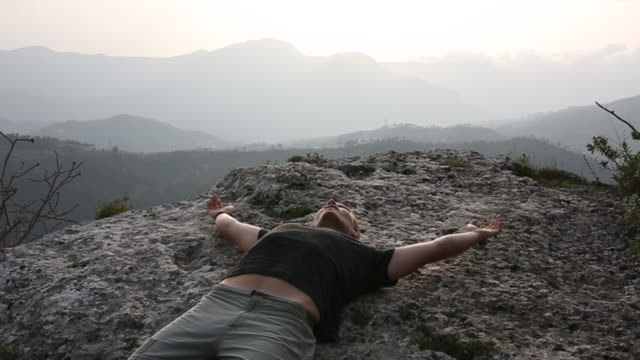 Young man relaxes on stone ledge, above valley, distant hills