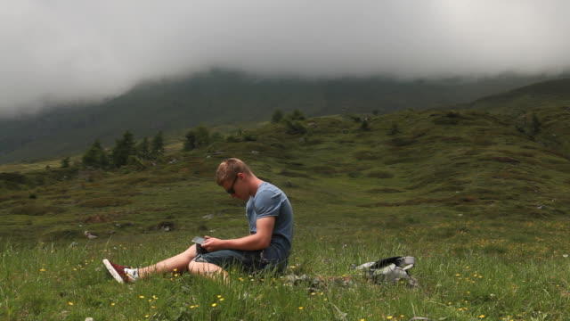 young man relaxes with tablet in alpine meadow as mist passes by overhead - adagiarsi video stock e b–roll