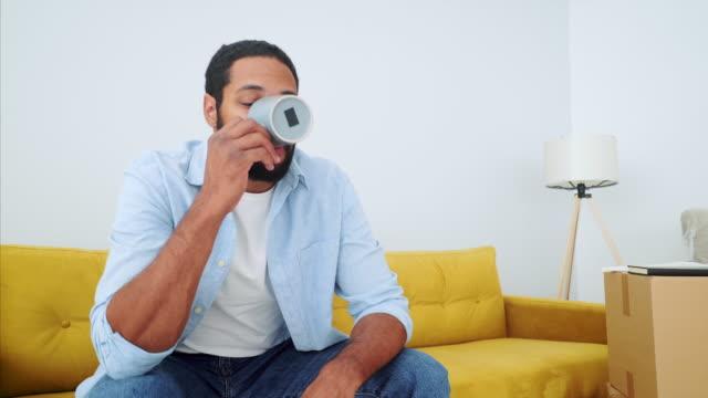 vídeos de stock, filmes e b-roll de homem novo que relaxa e que ejoying uma bebida em casa. - coffee drink