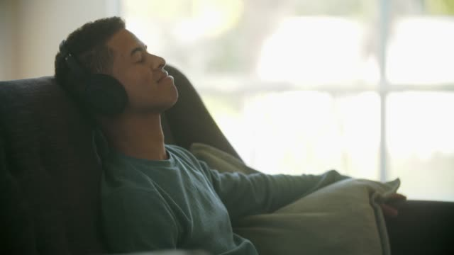 cu young man relaxing at home - music stock videos & royalty-free footage