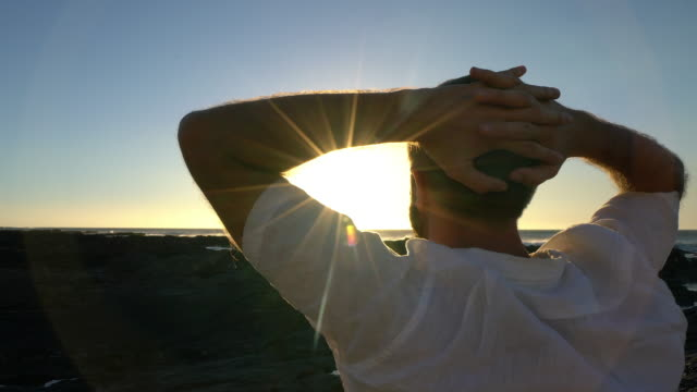 young man relaxing by the sea at sunset - hands behind head stock videos & royalty-free footage