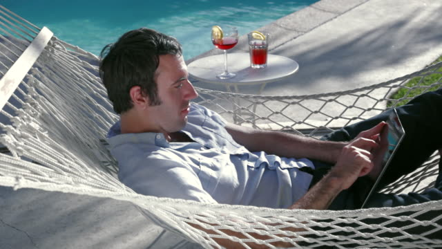 ms young man relaxing in hammock and reading on tablet computer / santa monica, ca, united states    - casual clothing stock videos & royalty-free footage