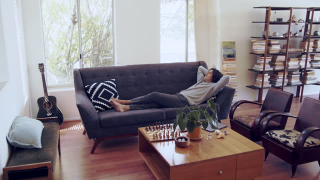 ws young man relaxing in his living room - lying on back stock videos & royalty-free footage