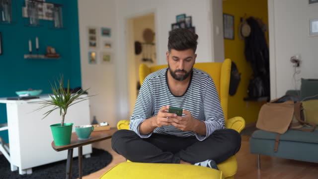 junger mann entspannt in seiner gemütlichen wohnung - vollbart stock-videos und b-roll-filmmaterial