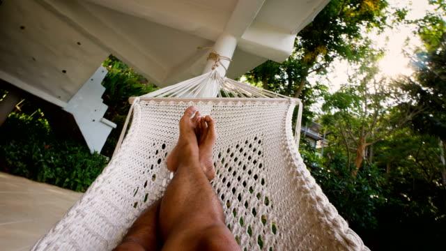 junger mann zum entspannen in der hängematte auf tropischen resort, thailand - hängematte stock-videos und b-roll-filmmaterial