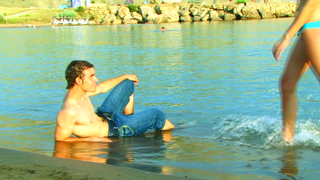 young man relaxing on the beach - tan stock videos and b-roll footage
