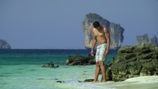 ws young man relaxing on tropical beach, krabi, thailand - see other clips from this shoot 1459 stock videos and b-roll footage