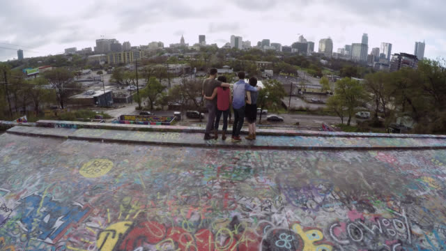 Young man releases drone and hugs friends as drone lifts off over Graffiti Park in Austin, Texas