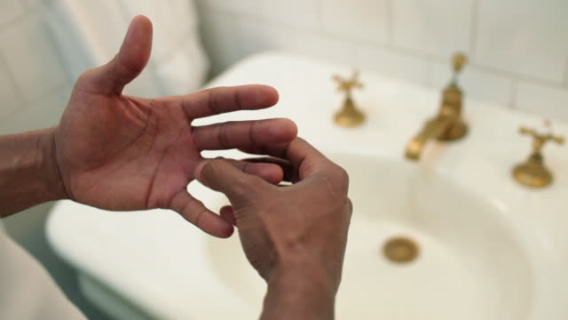 Young man removing wedding ring at bathroom sink