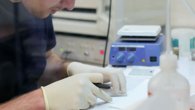 young man researcher preparing scientific samples for examination - centro di ricerca video stock e b–roll