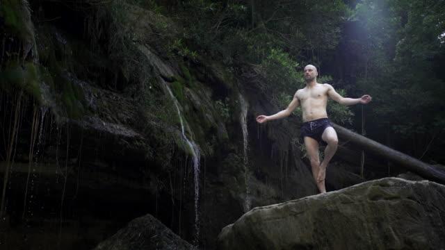 Young man resting among waterfalls