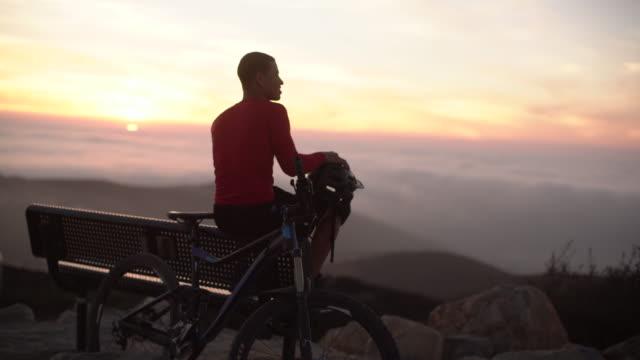 vidéos et rushes de ws young man resting with his mountain bike on top of a mountain - noir américain