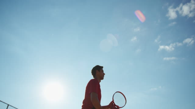 Young man returning tennis ball with forehand strokes in slow motion