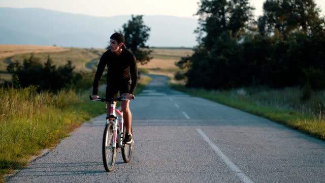 vídeos de stock e filmes b-roll de young man rides a bike on a country road - 25 29 anos
