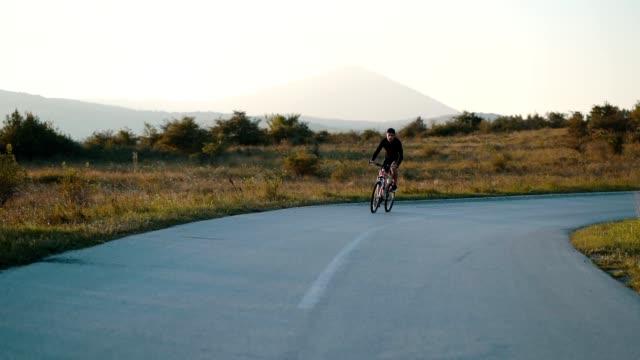 junger mann reitet ein fahrrad auf einer landstraße - nur junge männer stock-videos und b-roll-filmmaterial