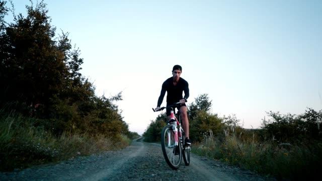 junger mann reitet ein fahrrad auf der landstraße - nur junge männer stock-videos und b-roll-filmmaterial