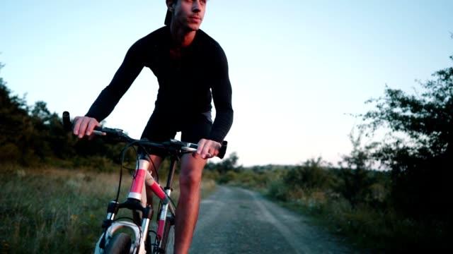 young man rides a bike on a rural road - mascolinità video stock e b–roll