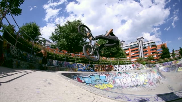 a young man rides a bmx bicycle in a concrete skate park. - slow motion - concrete点の映像素材/bロール