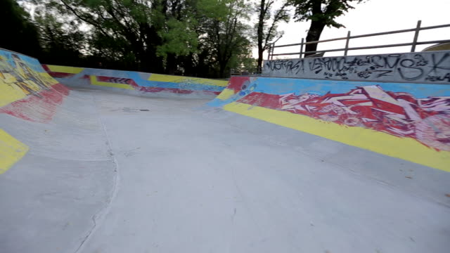 A young man rides a BMX bicycle in a concrete skate park.