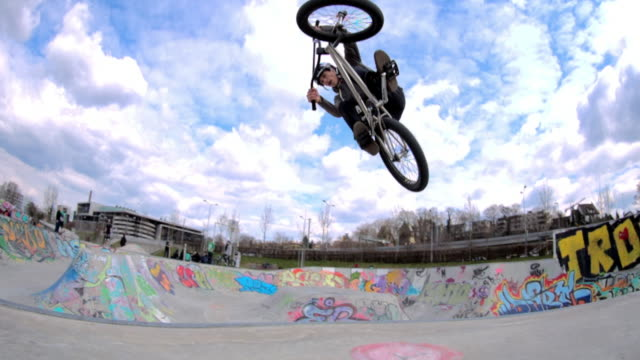 stockvideo's en b-roll-footage met a young man rides a bmx bicycle in a concrete skate park. - skateboardpark