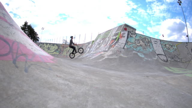 a young man rides a bmx bicycle in a concrete skate park. - skateboard park stock-videos und b-roll-filmmaterial