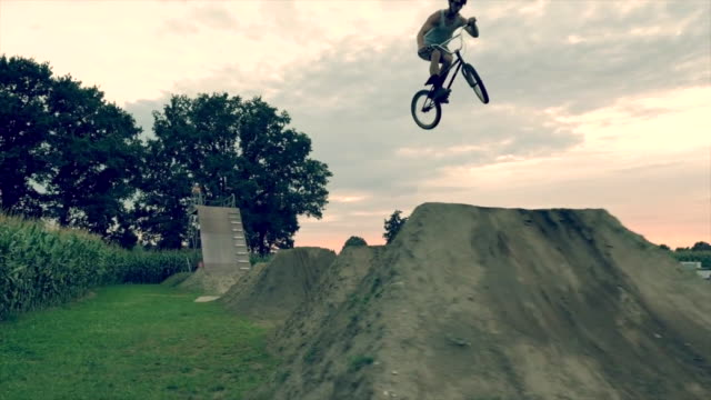a young man rides and jumping his bmx bike bicycle on an outdoor dirt track with jumps. - bicycle trail outdoor sports stock videos & royalty-free footage