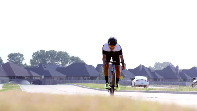 young man rides bicycle on residential street - racing bicycle stock videos and b-roll footage