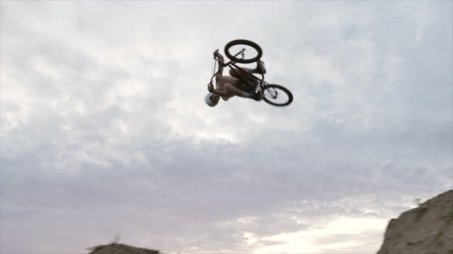 stockvideo's en b-roll-footage met a young man rides his bmx bike bicycle and does a 360 trick stunt on an outdoor dirt track with jumps. - acrobatiek