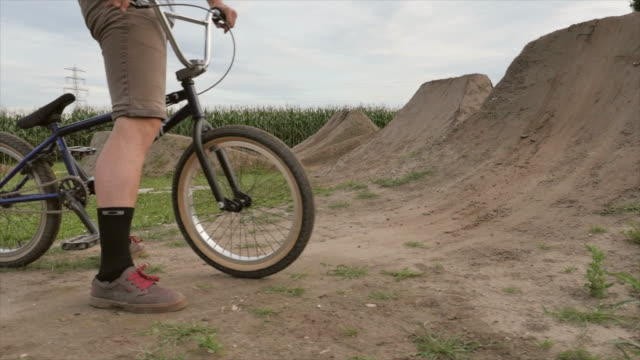 a young man rides his bmx bike bicycle on an outdoor dirt track with jumps. - bicycle trail outdoor sports stock videos & royalty-free footage