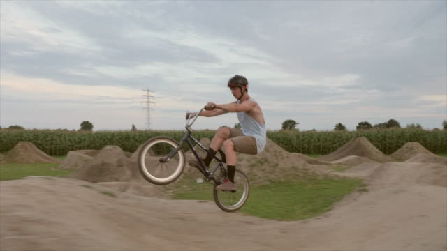 vidéos et rushes de a young man rides his bmx bike bicycle, wheelie trick on an outdoor dirt track with jumps. - exploit sportif