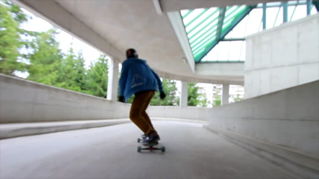 A young man rides his skateboard down a parking ramp.