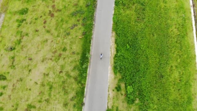 若い男が自転車に乗って川の近くの道 - 車輪点の映像素材/bロール