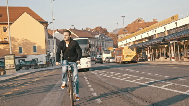 slo mo junger mann auf einem fahrrad in der stadt - moving past stock-videos und b-roll-filmmaterial