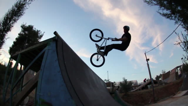 a young man riding a bmx bicycle. - bmx stock-videos und b-roll-filmmaterial