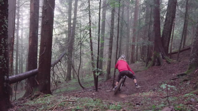 a young man riding a mountain bike in fog, biking in a forest full of trees. - motorcycle biker stock videos & royalty-free footage