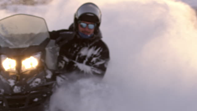slo mo young man riding a snowmobile - northern europe stock videos & royalty-free footage