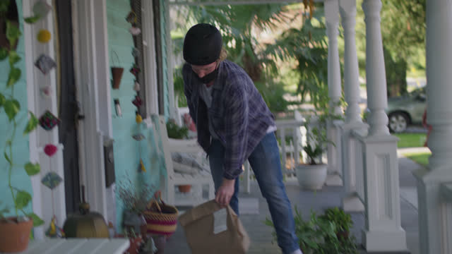 young man riding bike contactlessly delivers package to woman's home - paper bag stock videos & royalty-free footage