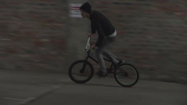 vídeos de stock e filmes b-roll de ms, ts, young man riding bmx bike in garage, capetown, south africa - corrida de bicicleta