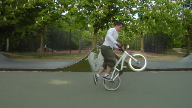 vídeos de stock, filmes e b-roll de ws young man riding bmx bike in park, berlin, germany - corpo inteiro