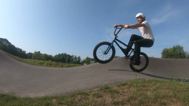 junger mann reitet bmx fahrrad in sonnigen park, zeitlupe - einzelner mann über 30 stock-videos und b-roll-filmmaterial