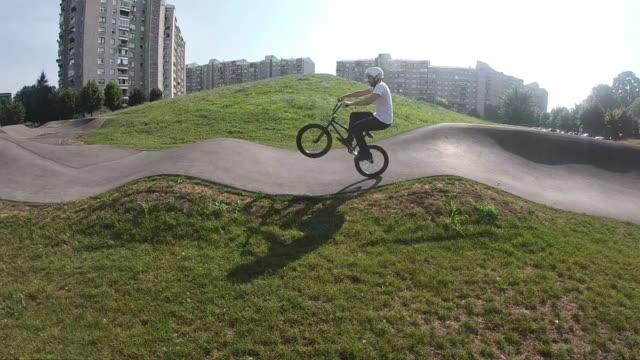 vídeos y material grabado en eventos de stock de joven montando bicicleta bmx en el parque soleado, cámara lenta - motociclista