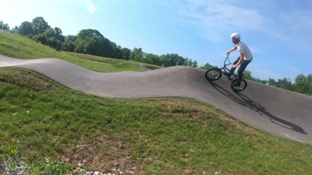 vídeos y material grabado en eventos de stock de joven montando bicicleta bmx, cámara lenta - motociclista
