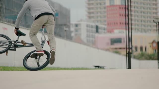 vídeos de stock e filmes b-roll de young man riding bmx. - câmara à mão