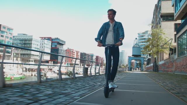 vidéos et rushes de jeune homme conduisant le scooter électrique de coup de pied sur le sentier - vie citadine