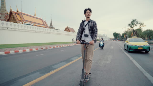 young man riding electric push scooters in bangkok city - sustainable tourism stock videos & royalty-free footage