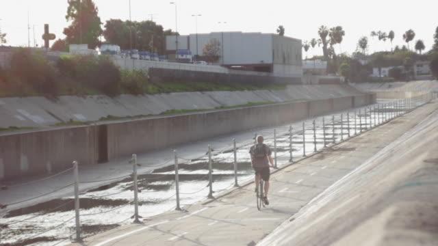 vídeos de stock, filmes e b-roll de a young man riding his bicycle on a bike path by a creek. - goodsportvideo