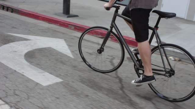 A young man riding his bike on the streets of a residential neighborhood.