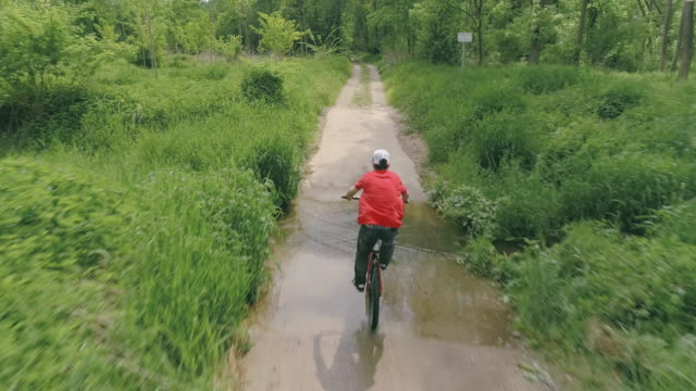 AERIAL Young man riding his mountain bike through a puddle