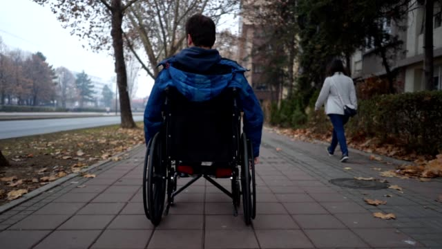 young man riding in his wheelchair along sidewalk - wheelchair stock videos and b-roll footage