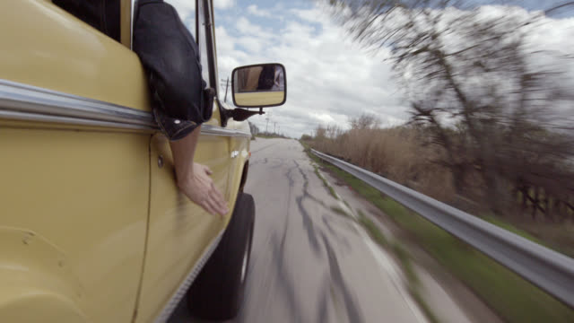 vídeos y material grabado en eventos de stock de young man riding in passenger seat of classic bronco holds hand out the window and drums on the car door - estados de la costa del golfo